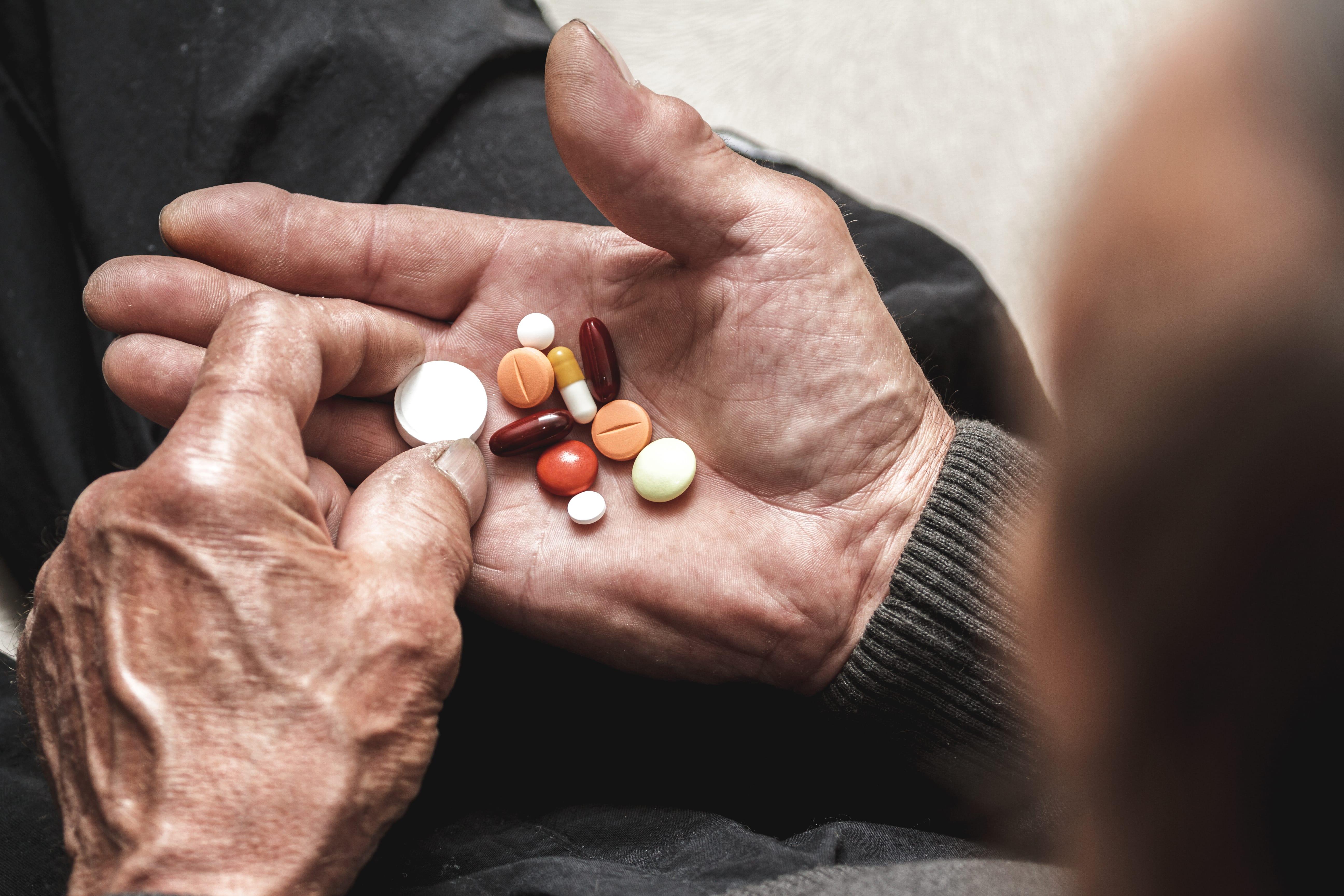 shutterstock_Senior's hand-pills-min